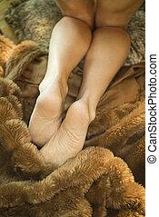 Woman on fur. - Caucasian mid adult female legs kneeling on...