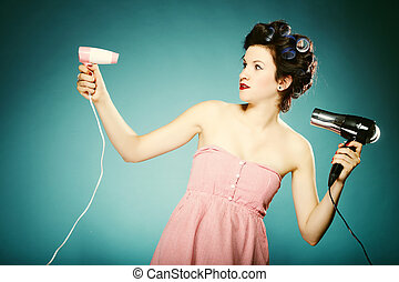 Funny girl in curlers with hairdryer styling hair - young...