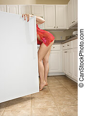Woman in refrigerator. - Caucasian young woman in sexy red...