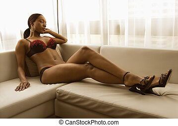 Woman in lingerie. - Young African American woman reclining...