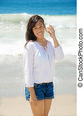 Beautiful woman with seashell on the beach - Beautiful...
