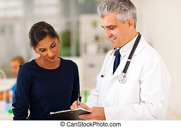 senior doctor checking patients test result - senior doctor...