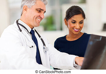 senior doctor examining patient x-ray - happy senior doctor...