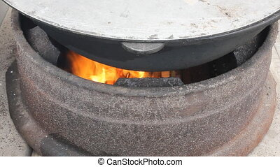 Traditional way of preparing food in a caldron