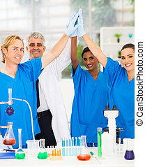 successful team of scientists high five in lab