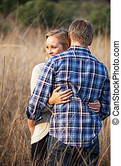 Young adult couple hugging in tall grass outside