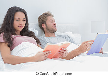 Couple reading in their bed - Couple reading peacefully in...