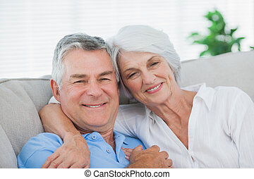 Couple relaxing on the couch - Mature couple relaxing on the...