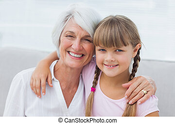 Cute girl and granny sitting on the couch