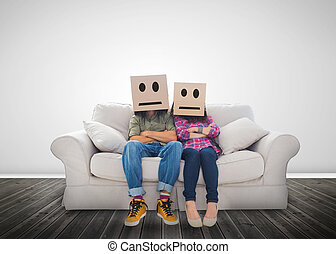 Couple sitting on couch with cardboard boxes over their head...