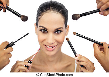 Beautiful woman encircled by make up brushes