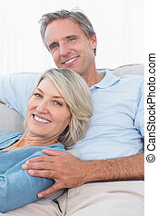 Smiling couple relaxing at home