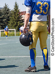 American football player out of the game, waiting