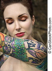 Nude tattooed woman. - Close-up of attractive Caucasian nude...