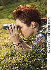 Woman spying. - Attractive tattooed Caucasian woman lying on...