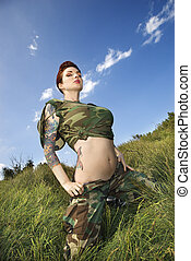 Woman in fatigues. - Attractive tattooed Caucasian woman in...
