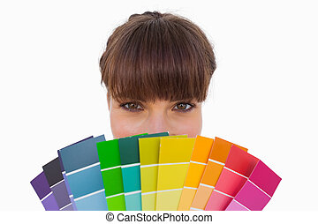Happy woman with fringe showing colour charts close up