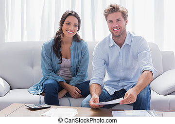 Couple doing their accounts sat in a couch - Happy couple...