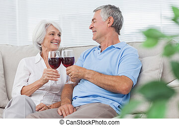 Couple clinking their glasses of red wine - Mature couple...