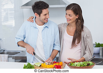 Man chopping vegetables next to his pregnant partner in the...