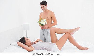 Shirtless man offering flowers to his girlfriend in bed