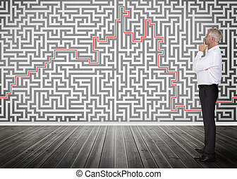 Thoughtful businessman looking at a maze on a wall -...