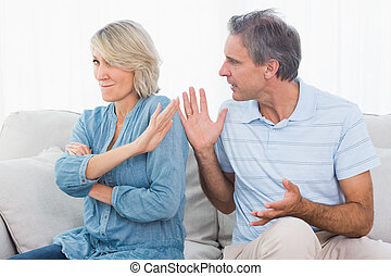 Man pleading with his wife after an argument at home on...