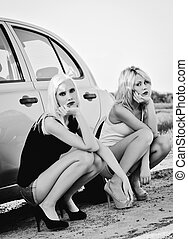 Two beautiful blonde girls sitting near broken car and waiting for help