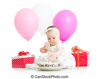 baby girl touching light on birthday cake