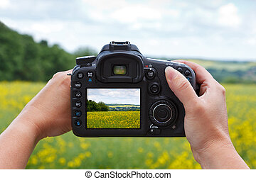 Taking a photo with a dslr camera - A woman using the rear...