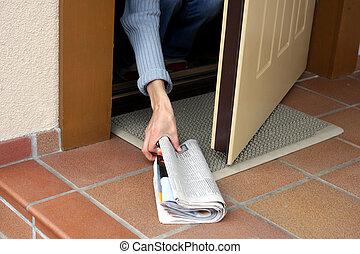 Morning newspaper - Woman picking up morning paper through...