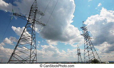 panorama with tall electric masts against cloudy sky
