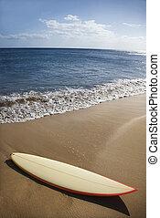 Surfboard on Maui beach. - Surfboard on sandy beach with...