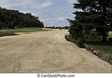 new road construction - large grader working on a section of...