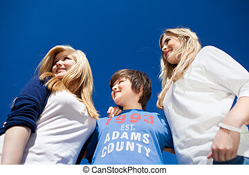 Three teenagers under a blue sunny sky - Low angle portrait...