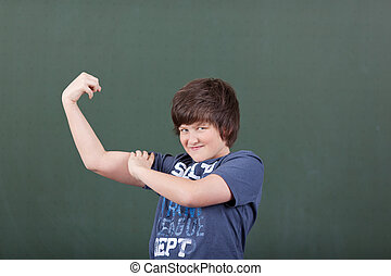 Cute young boy showing off his biceps flexing his arm in...