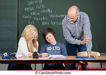 Two students being helped by a teacher - Two young teenage...