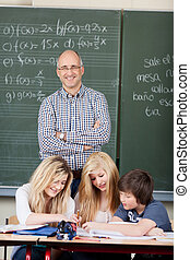 Smiling male teacher with his students