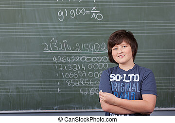 Young boy solving a maths problem in class standing with a...