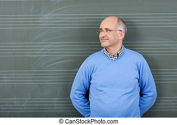 Happy satisfied male teacher standing with his hands behind...