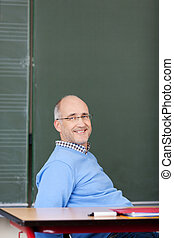 Smiling male teacher relaxing in the classroom reclining in...