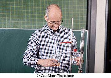 Teacher preparing a chemistry experiment - Attractive mature...