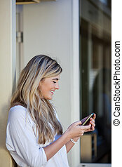 Beautiful girl sending an sms on a mobile - Beautiful young...