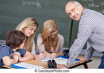 Friendly male teacher in the classroom looking back over his...