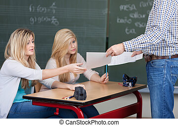 Teacher handing out marked assignments - Male teacher...