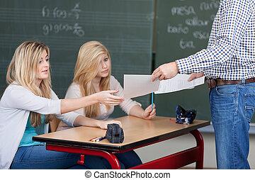 Teacher handing out marked assignments - Male teacher...
