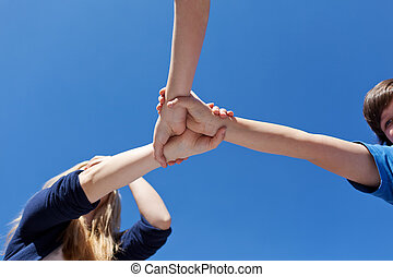 Friends Holding Hands Against Clear Blue Sky - Low angle...
