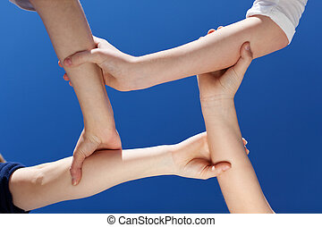 Closeup Of Friends Holding Hands Against Clear Blue Sky -...