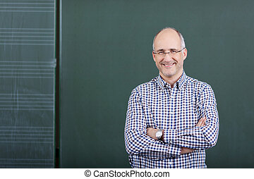 Professor With Arms Crossed Standing Against Chalkboard