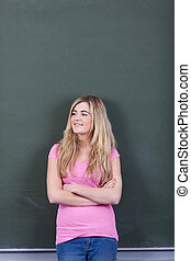Girl With Arms Crossed Looking Away While Leaning On Chalkboard
